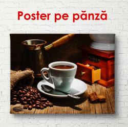 Poster, O ceașcă și o râșniță de cafea pe masă