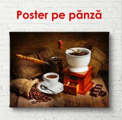 Poster, O ceașcă albă și o râșniță de cafea pe masă