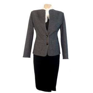Jachetă gri închis cu fustă neagră.
