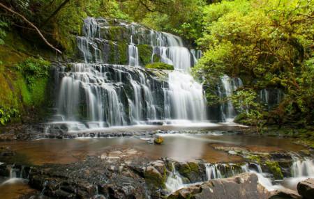 Fototapete, O cascadă fermecătoare și pietre mari pe fundalul unor copaci